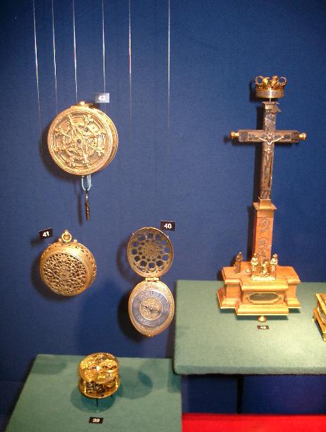 Till vänster om krusifix-uret ses ett fickur från 1500-talet, sannolikt Tyskland, med genombruten boett av mässing, försilvrad sifferring, spindelgång med stångbalans.