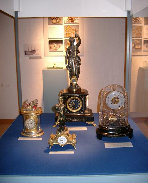 Till höger: Bordsur, Bulle-Patent, omkring 1930-tal. Batteridriven silverfärgad urtavla. Till vänster: ur med dansande porslinsdockor. I mitten, förgrunden: Bordspendyl av förgylld och patinerad metall från 1800-talets senare del.